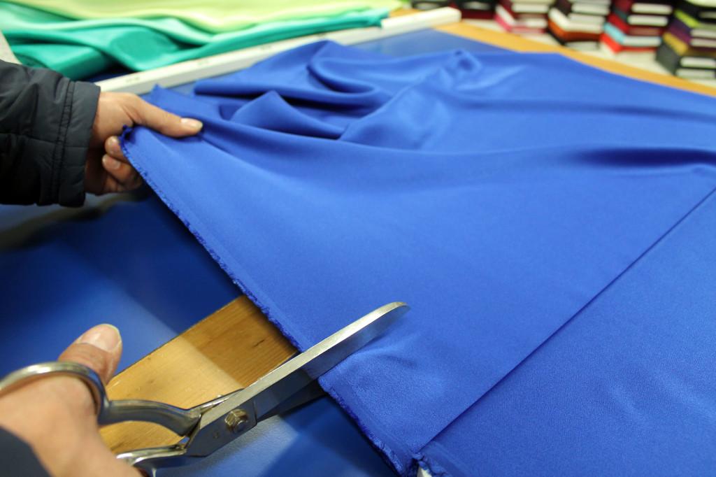 Tagliando un tessuto blu sul tavolo da lavoro dell'Arcobaleno.